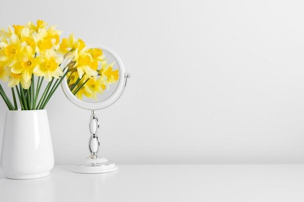 Желтые цветы нарциссы в вазе и отражение цветов в зеркале