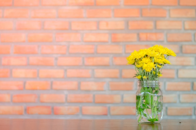 Yellow flowers in glass on wood table with brick background,copy space.