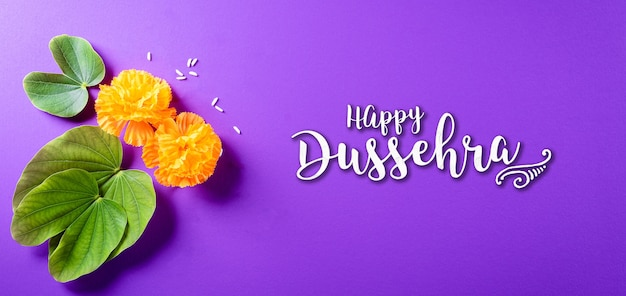 Yellow flowers green leaf and rice on purple pastel background dussehra greeting