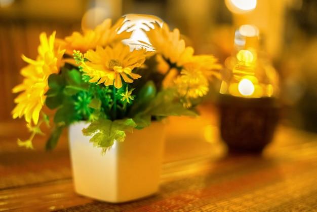 램프 옆에 있는 나무 탁자에 있는 흰색 냄비에 있는 노란색 꽃과 형태의 촛불