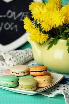 Желтые цветы в декоративном чайнике и вкусные миндальное печенье на деревянном