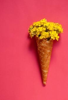 ラズベリーの背景にアイスクリームコーンの黄色い花。