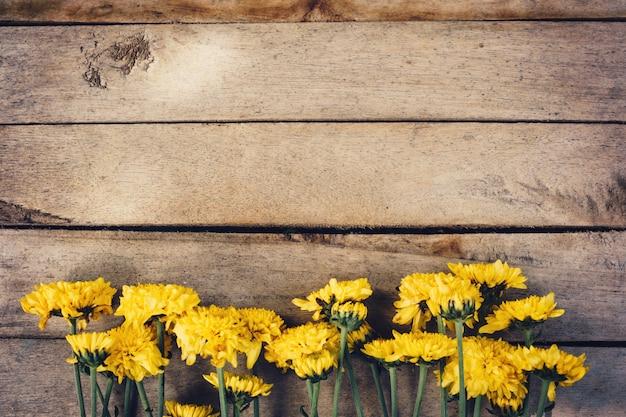 Желтые цветы букета, вид сверху на деревянной текстуре фона с копией пространства