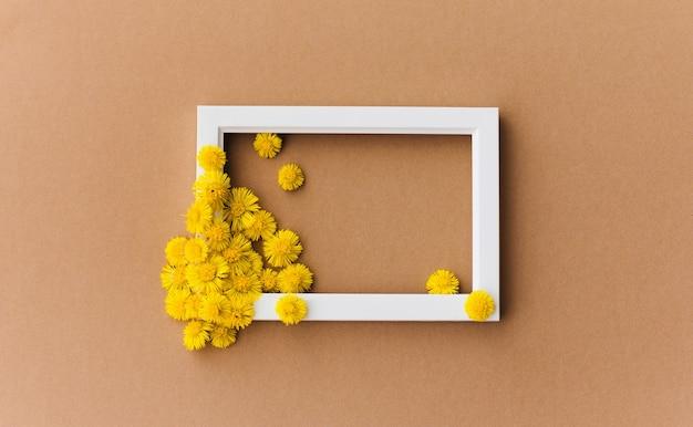 갈색 배경에 고립 된 흰색 프레임에 노란색 꽃