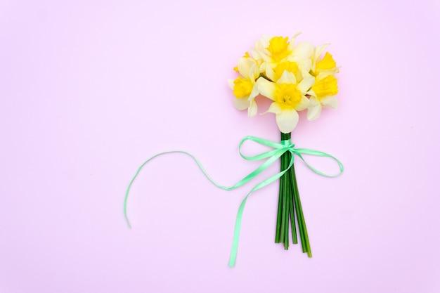 ピンクの背景に黄色い花。花束の水仙、春のギフトのコンセプト。