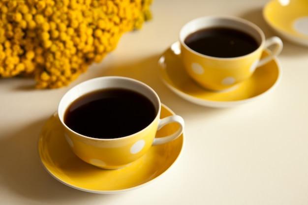 テーブルの上の黄色い花-白い背景の上の2つの黄色いコーヒーカップ、コーヒーブレイクとカフェイン中毒の概念。ヴィンテージデザインとレトロなスタイル