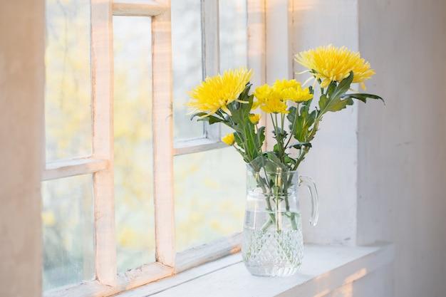 Желтые цветы на белом подоконнике