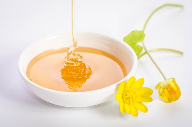 Yellow flowers and pouring honey into white bowl