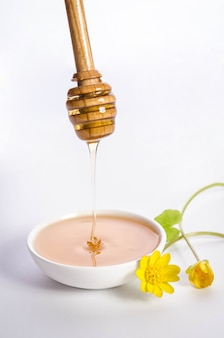 Yellow flowers and pouring honey into the white bowl