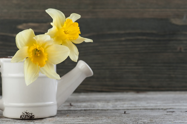 Yellow flowers in vase on wooden table. copyspace