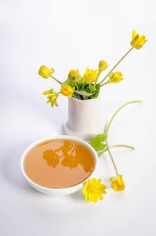 Yellow flowers and white bowl with honey