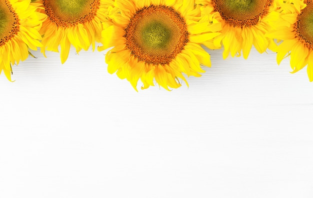 Yellow flowers on a white wooden background top view autumn background with agricultural crop