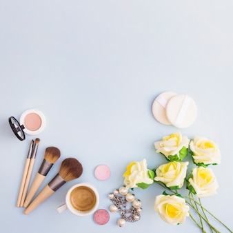 Yellow flowers with cosmetic product and coffee cup on white background