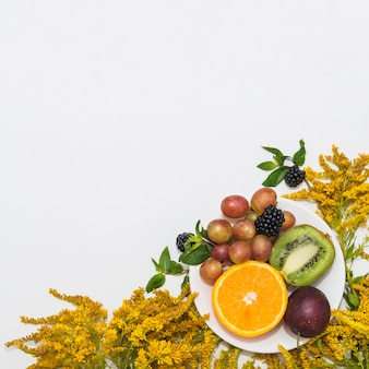Yellow flowers with fruits on plate against white background