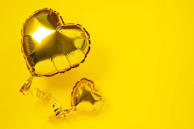 Yellow foil balloons in shape of heart on yellow