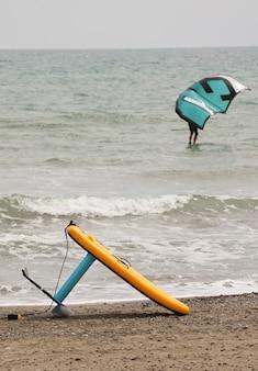 라이더 항해와 모래 해변 배경에 노란색 foilboard