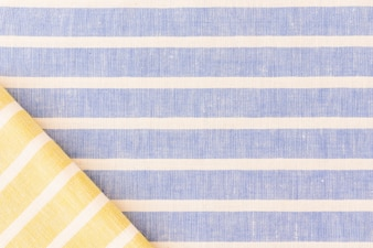 Yellow folded fabric on linen texture backdrop