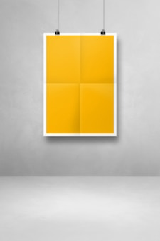 Yellow folded poster hanging on a clean wall with clips. blank mockup template