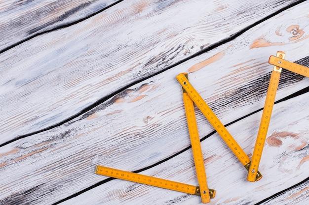 灰色の木製の背景に黄色の折りたたみ定規