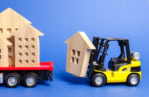 A yellow forklift loads a wooden figure of a house into a truck.