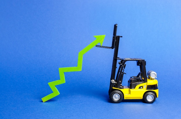 Yellow forklift raises a big green arrow up growth in production rates and development of industry
