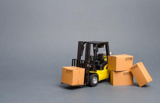 段ボール箱と黄色のフォークリフト。商品の売り上げ、生産を増やす。交通手段