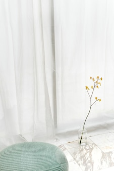 Yellow forsythia in a cleared-vase on a white marble floor by a white curtain