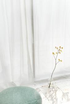 흰색 커튼으로 흰색 대리석 바닥에 투명 꽃병에 노란색 개나리