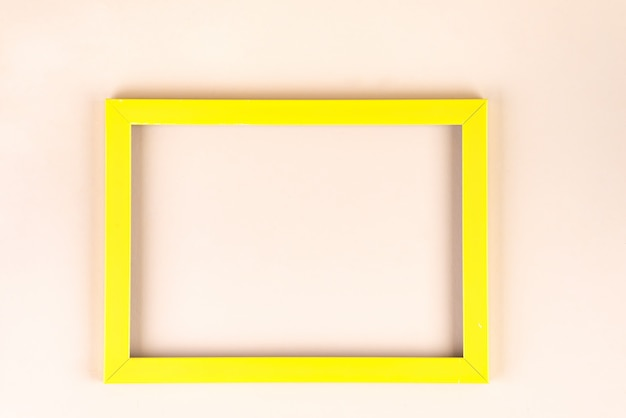 Yellow frame isolated on beige background with copyspace, flat lay