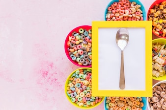 Yellow frame with spoon on bowls of cereals