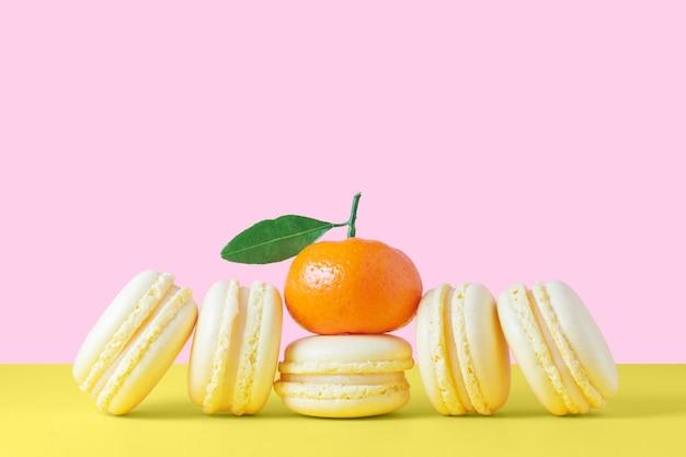 Желтые французские пирожные с миндальным печеньем с лимонным кремом на желто-розовом фоне любовь
