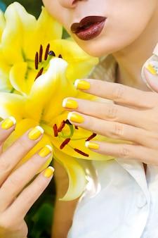 夏のクローズアップで黄色いユリを持つ女の子のための黄色いフレンチマニキュア。