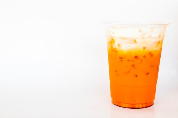 白い背景の上のプラスチックカップに黄色の新鮮な飲み物