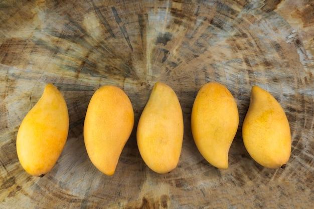 Желтый свежий стол из натурального дерева манго. тропический фрукт манго.