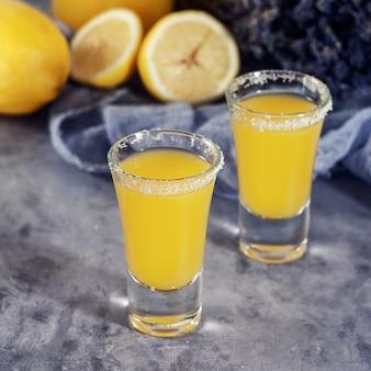 Yellow fresh shot cocktail or lemonade with lemon