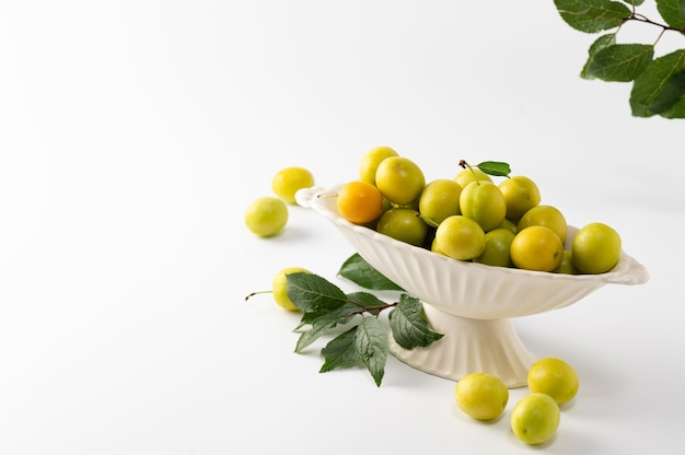 Yellow freshly torn cherry plum with green leaves in a ceramic vase on a white background, empty space for text