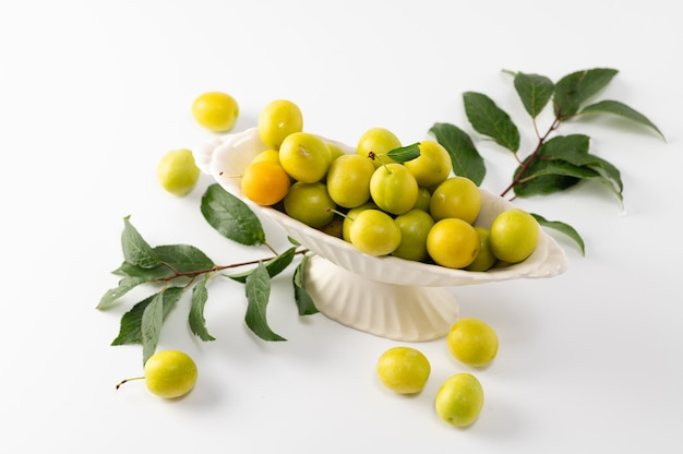 Yellow freshly torn cherry plum with green leaves in a ceramic vase on a white background