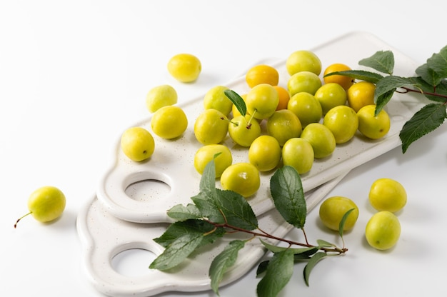 Yellow freshly torn cherry plum with leaves, ceramic boards for serving on a white background