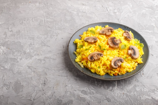 Yellow fried rice with champignons mushrooms, turmeric and oregano on blue ceramic plate on a gray concrete surface. side view.