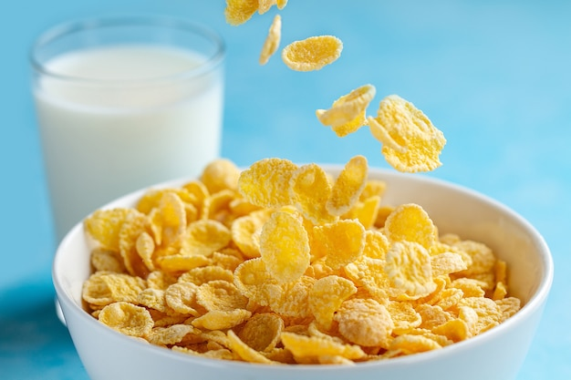 Yellow frosted corn flakes bowl and a glass of milk for dry, cereals breakfast