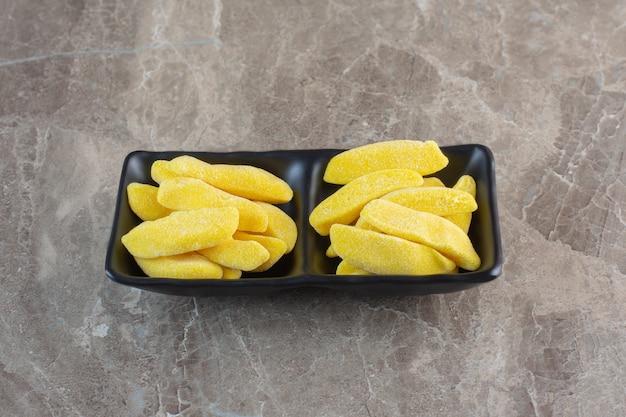 黄色いフルーツの歯ごたえのあるキャンディーn黒いセラミックボウル。