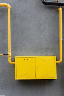 Желтая газовая труба с краном идет вдоль фасада нового многоэтажного дома.