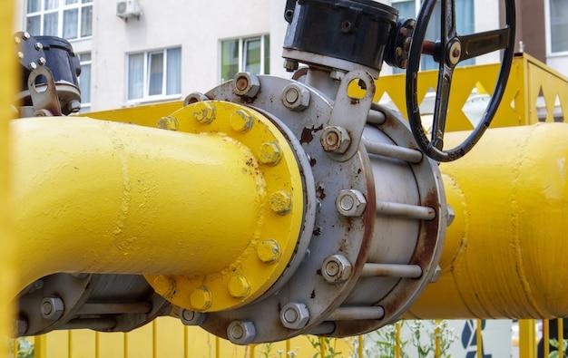 Желтая газовая труба с краном. арматура нефтепроводов в нефтегазовой отрасли. нефтегазоперерабатывающий завод с трубопроводной арматурой. промышленный предохранительный клапан.