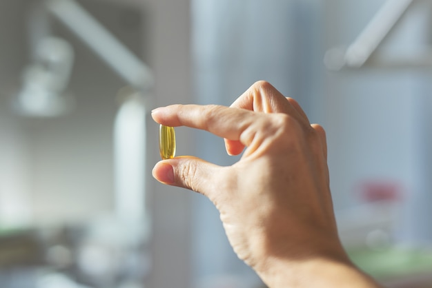 Yellow gel capsule of vitamin d, e, omega-3 in womans hand close-up