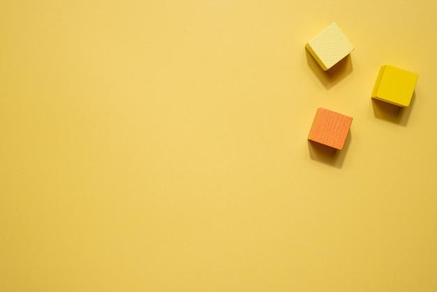 黄色の幾何学図形は静物画です。黄色の背景に木製のゲームキューブオブジェクト。正多面体フィギュア、シンプルコンセプトトップ