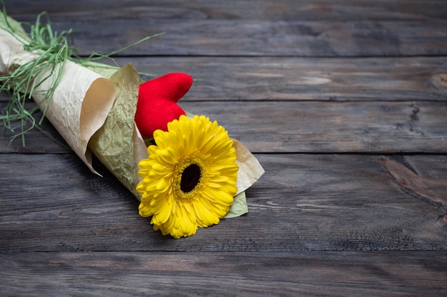 Yellow gerbera, red velvet heart in ecological natural paper packaging, beautifully designed, waste recycling. copy space.
