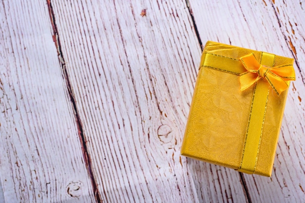 흰색 나무 테이블, 생일, 크리스마스 개념에 나비 리본 노란색 선물 상자. 선물 개념을 수락