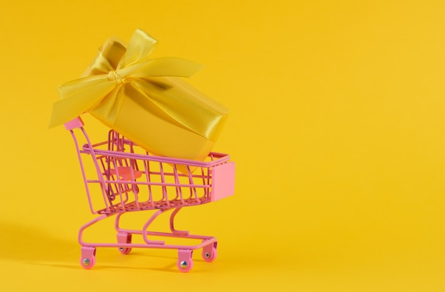 Yellow gift box with a silk bow in a miniature metal trolley on a yellow surface. party backdrop, surprise, seasonal sale