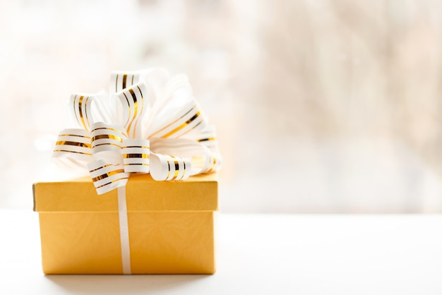 Yellow gift box wrapped in white and gold striped ribbon on light background.