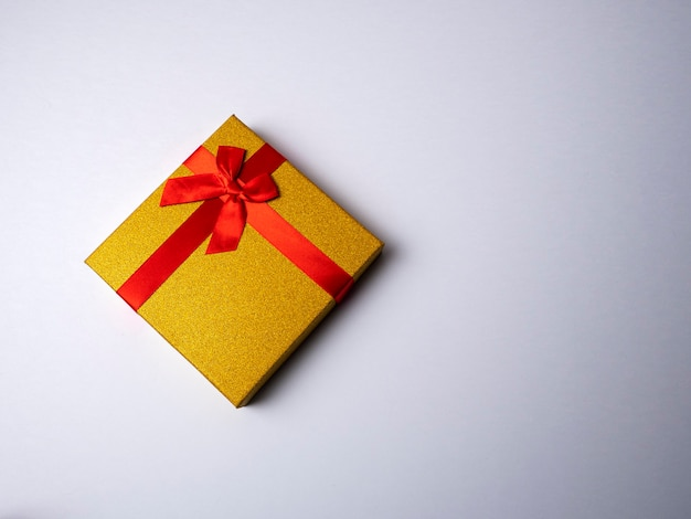 Yellow gift with a red ribbon in the form of a butterfly knot lies on a bright white background